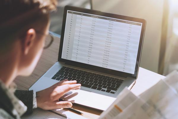 Mann sitzt am Rechner auf dem Zahlen zu sehen sind