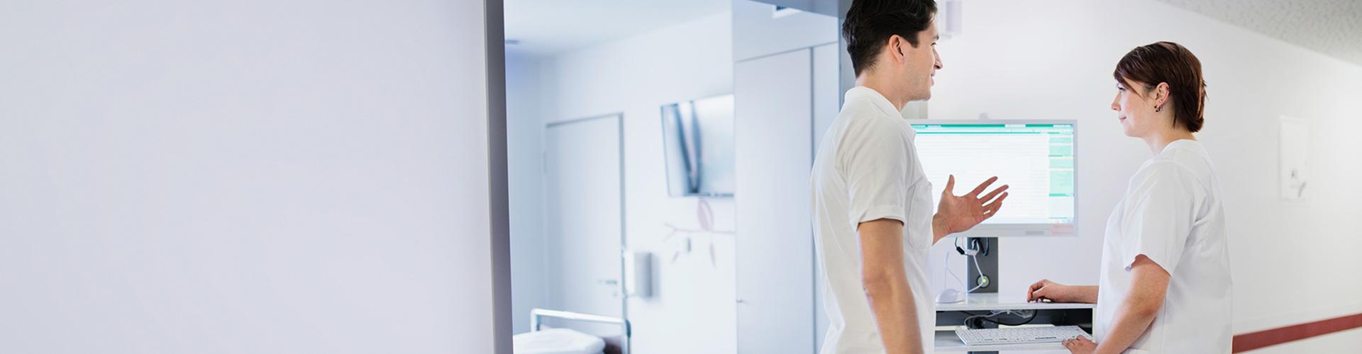 Ein Arzt spricht mit einer Krankenschwester auf dem Flur