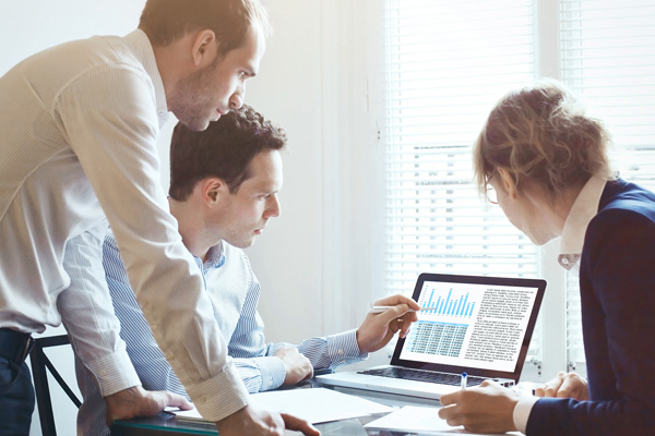 Zwei Männer und eine Frau schauen im Büro auf einen Laptop