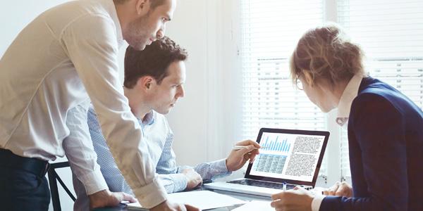 Drei Personen schauen auf ein Laptop