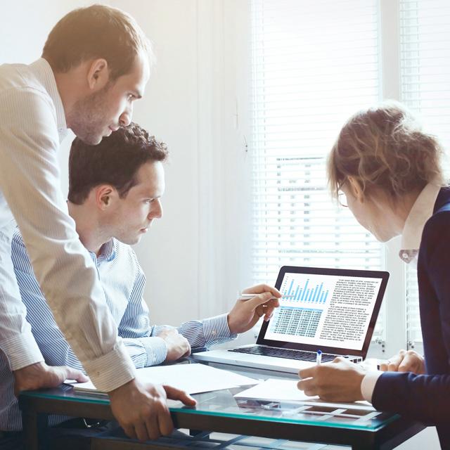 Eine Gruppe Mitarbeiter schaut auf einen Laptop