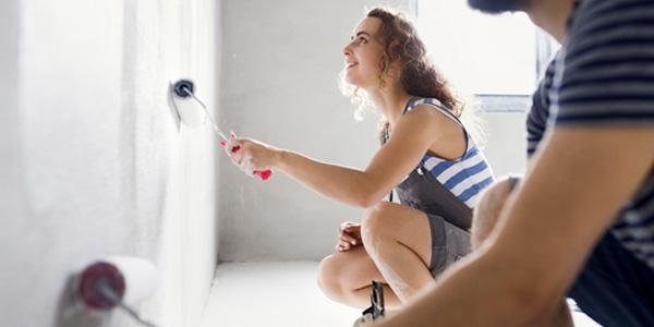 Junge Frau streicht ein Zimmer
