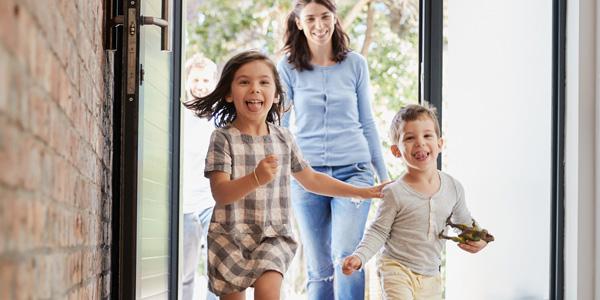 Frau und Kinder betreten ein Haus