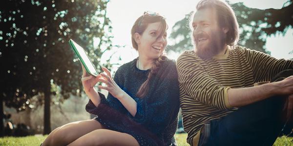 Frau und Mann mit Tablet im Park