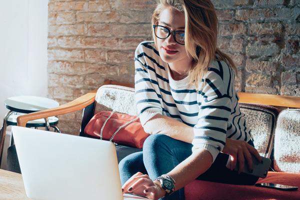 Junge Frau sitzt zu Hause vor dem Laptop
