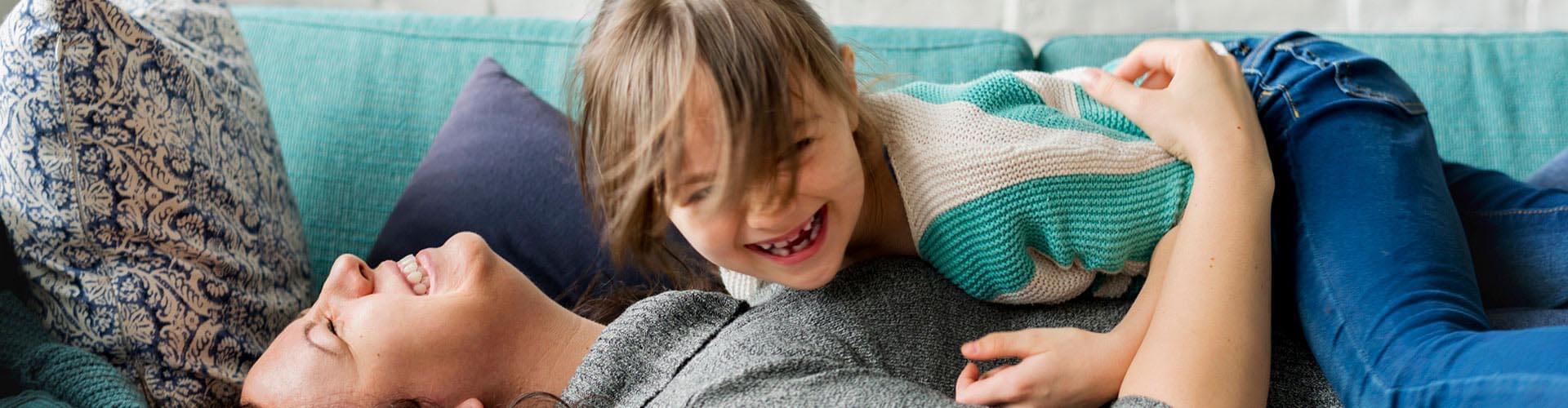 Frau und Kind liegen auf dem Sofa und freuen sich