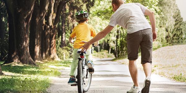 Vater lernt Sohn Fahrrad fahren