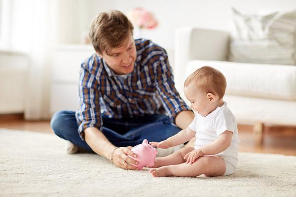 Vater und Kind sitzen auf dem Wohnzimmerboden und halten ein Sparschwein in den Händen