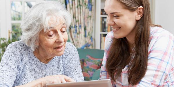 Junge Frau hilft älterer Frau am Laptop