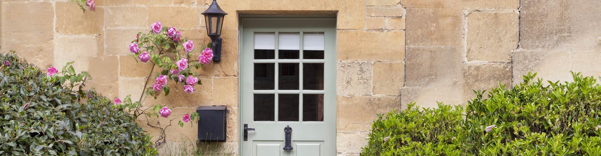 Alte Gemäuer mit Rosenbusch und einer Holztür