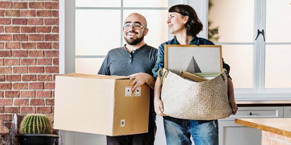 Frau und Mann mit Umzugskisten tragend in Wohnung