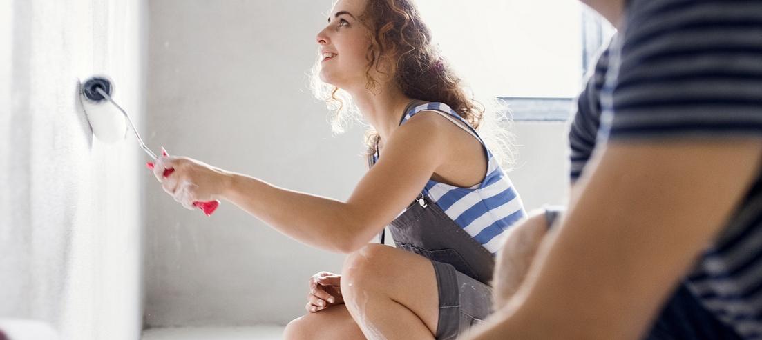 Ein junges Paar streicht in einer leeren Wohnung die Wände weis an