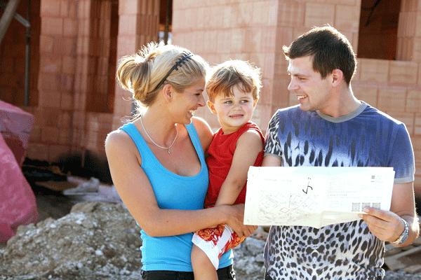 Ein junge Familie besichtigt ihre Baustelle