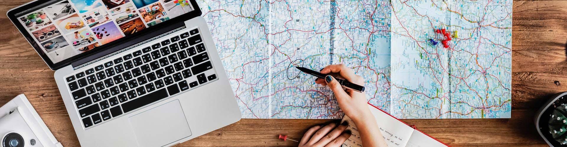 Frau sucht auf einer Weltkarte nach Ihrem nächsten Reiseziel