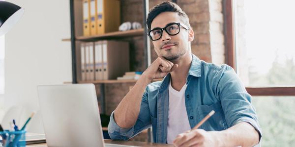 Mann überlegt am Schreibtisch
