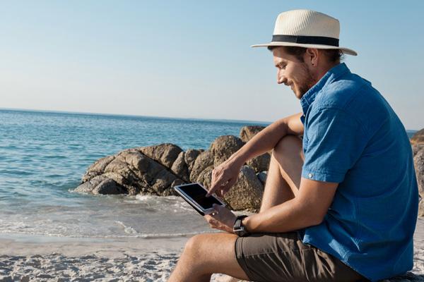 Mann sitzt im Urlaub am Strand