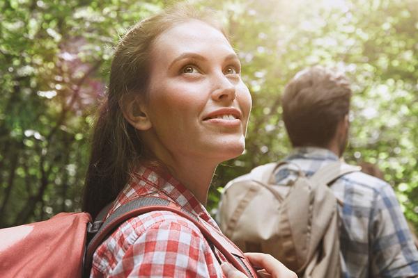Eine Frau mit Rucksack wandert durch einen Wald