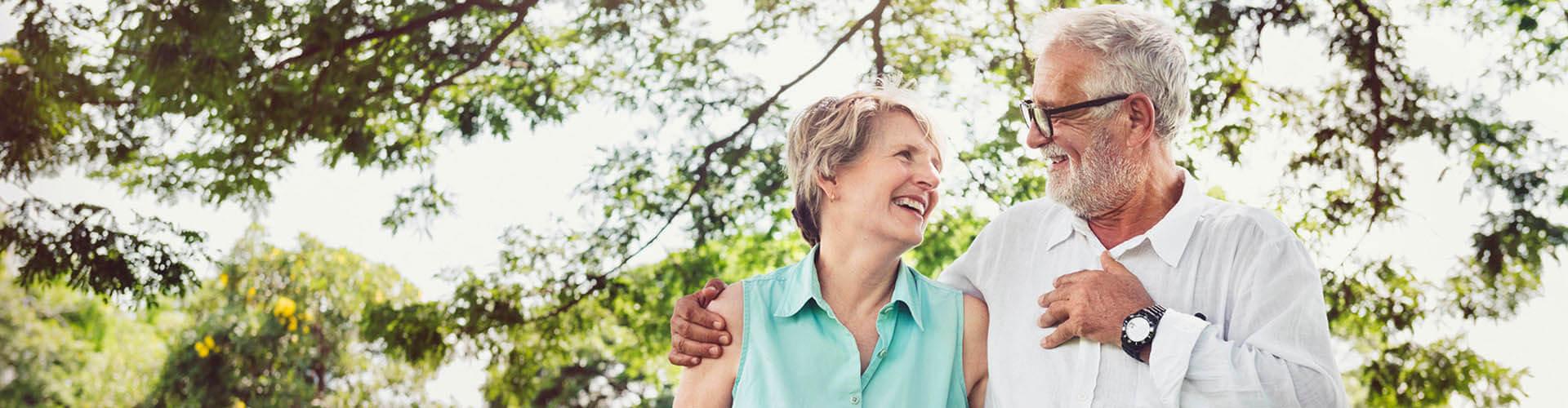 Ein älteres Ehepaar geht im Wald spazieren