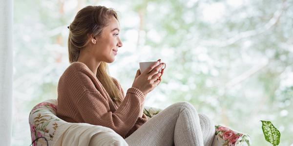 Frau mit Kaffeetase gemütlich im Sessel sitzend