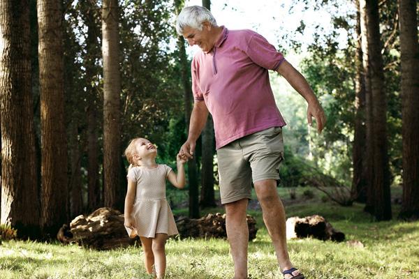 Opa läuft mit Enkeltochter Hand in Hand auf einem Waldweg