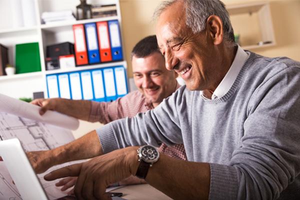 Älterer und jüngere Mitarbeiter arbeiten zusammen im Büro