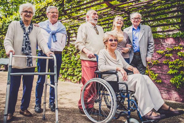 Eine Gruppe von Rentnern mit einer Rollstuhlfahrerin auf einem Weg