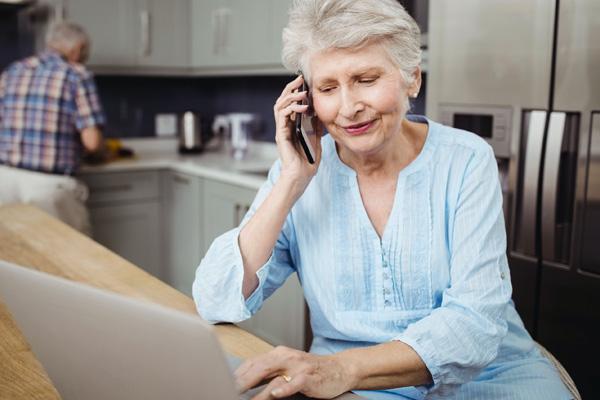 Eine ältere Dame sitzt am Laptop und telefoniert mit ihrem Smartphone