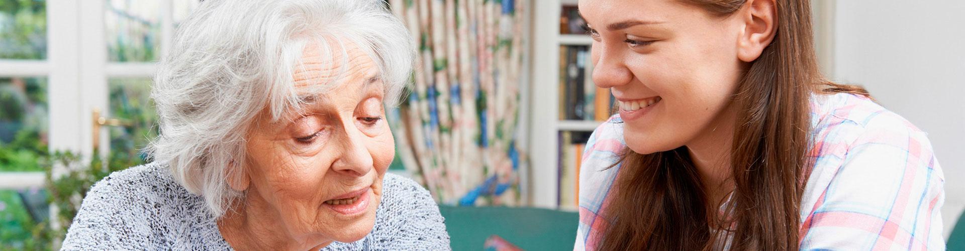 Eine ältere Dame lässt sich im Wohnzimmer von ihrer Enkeltochter etwas erklären