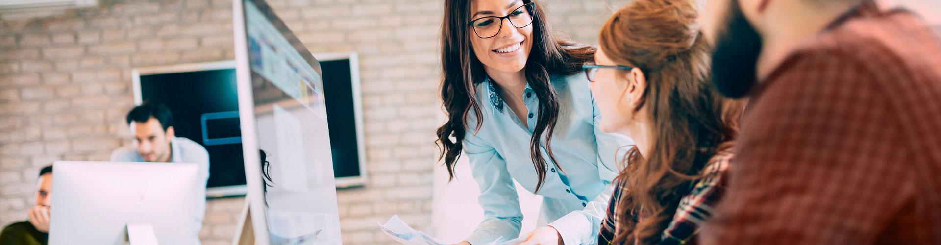 Frau erklärt einer Kollegin im Büro einen Arbeitsvorgang