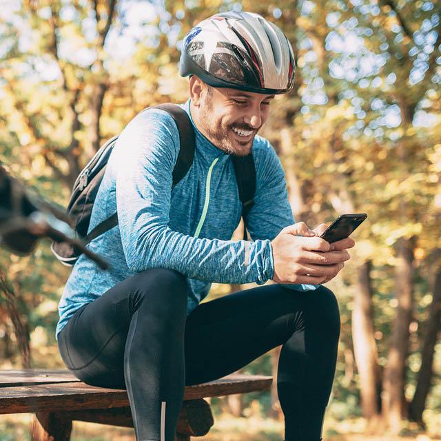Mann mit Fahrradhelm sitzt auf einer Parkbank und schaut auf sein Smartphone