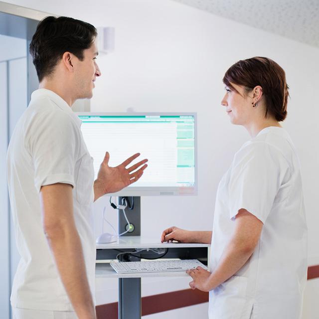 Ärztin und Pfleger diskutieren auf einem Flur