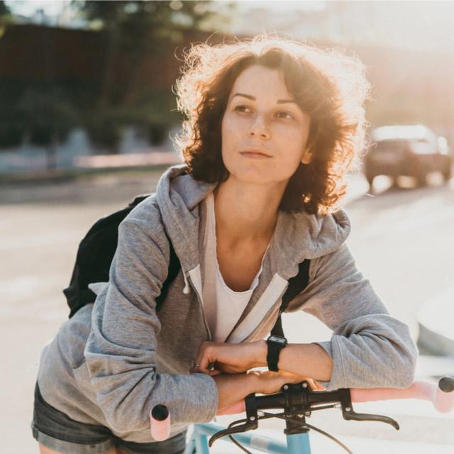 Frau lehnt sich an Fahrrad an
