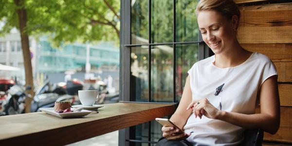 Frau sitz im Cafe und schaut auf Ihr Smartphone
