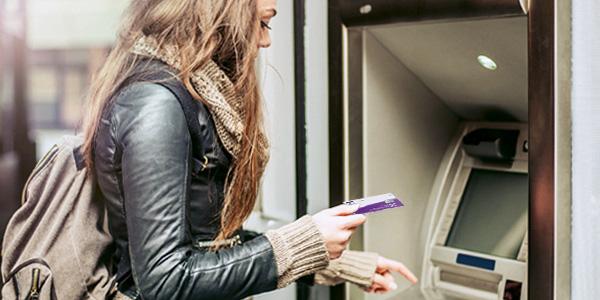 Eine junge Frau hebt am Automaten Bargeld ab.