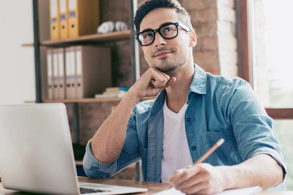 Mann am Laptop ist in Gedanken und macht Pläne