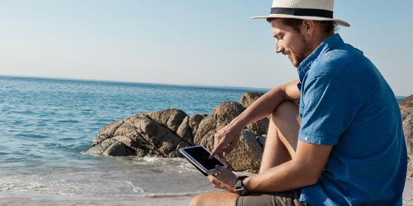 Mann mit Tablet am Meer
