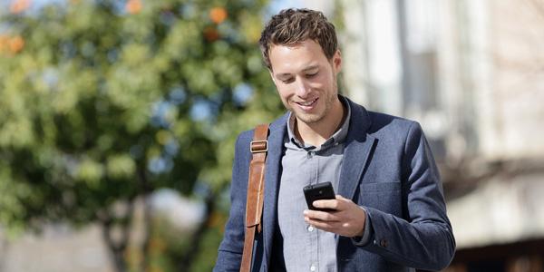 Mann schaut im Freien auf sein Smartphone