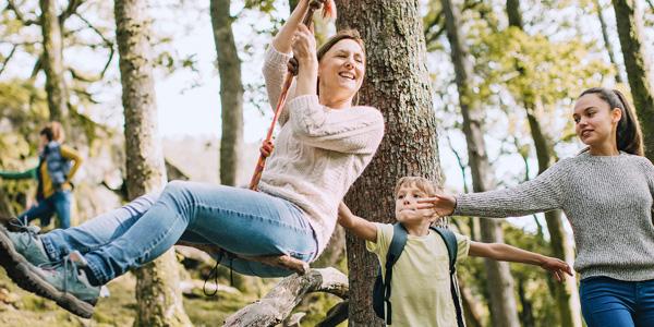 Mutter schwingt auf einem Seil und Kinder geben Schwung