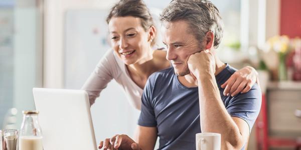 Frau und Mann schauen auf einen Laptop