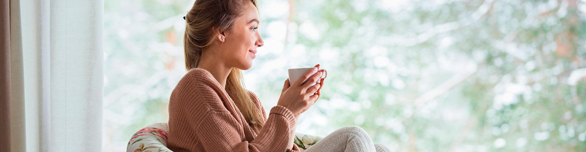 Frau sitzt im Sessel mit einer Tasse Tee in der Hand und schaut zufrieden vor sich