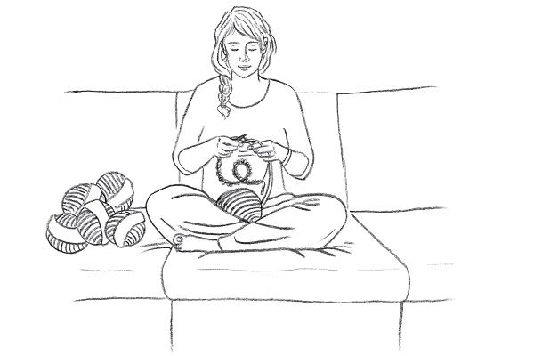 Junge Frau sitzt auf einem Sofa und beginnt zu stricken
