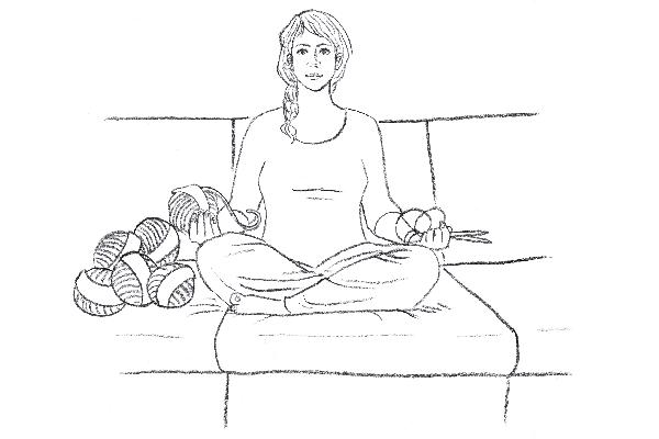 Junge Frau sitzt auf einem Sofa mit einem Bündel Wollknäuele