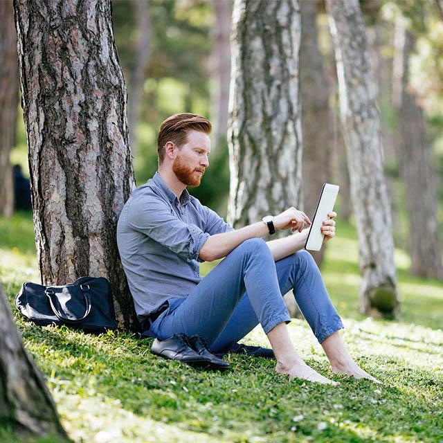 Mann sitzt mit einem Tablet an einen Baum gelehnt im Grünen