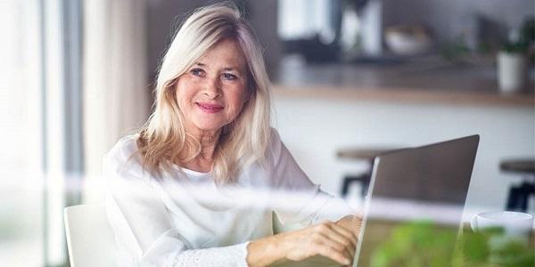 Mann auf dem Sofa liegend hält Kind mit ausgestreckten Armen über sich