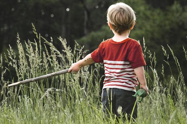 Junge streift mit Stock in der Hand durch hohes Gras