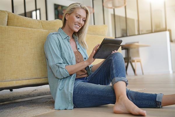 Frau sitzt vor einem Sofa mit einem Laptop in den Händen